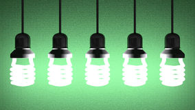 Hanging glowing spiral light bulbs on green Royalty Free Stock Photos