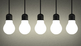 Hanging glowing tungsten light bulbs on gray Royalty Free Stock Photo