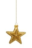 Hanging gold star Christmas ornament over white. Single hanging gold star Christmas ornament isolated on white royalty free stock photography