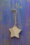 Hanging handmade wooden star on wooden purple background for chr Stock Photography