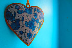 Hanging heart on blue background Stock Photos