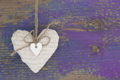 Hanging heart and purple wooden background in country style. Hanging heart and purple wooden background in country style - greeting card royalty free stock image