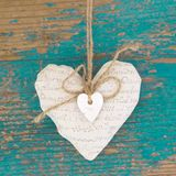 Hanging heart and turquoise wooden background in country style.