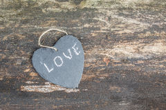 Hanging heart and wooden background in country style. Hanging heart and wooden background in country style - greeting card royalty free stock image