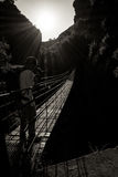 Hanging high I. Hanging bridge over a deep and dark canyon against the sun Stock Images