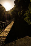 Hanging high II. Hanging bridge over a deep and dark canyon against the sun Royalty Free Stock Photo