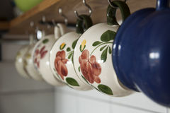 Hanging on hooks coffee cups in kitchen. Hanging coffee cups on hooks Royalty Free Stock Image