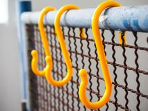 Hanging Hooks. Hanging yellow hooks at the blue fence Royalty Free Stock Photography