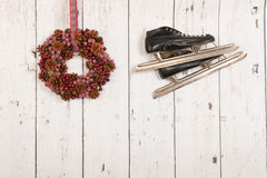 Hanging ice skates on wooden wall Stock Images