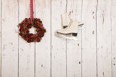 Hanging ice skates on wooden wall Stock Photo