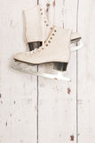 Hanging ice skates on wooden wall Stock Photography