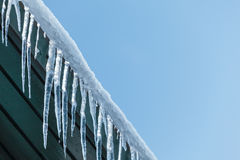 Hanging icicles on a roof Royalty Free Stock Photography