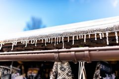 Hanging icicles from the roof of a wooden building on a winter frosty day, a lot of snow on the roof, a visible plastic gutter and royalty free stock images