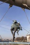 Hanging iron figures balancing on ropes on footbridge Bernatka,Krakow, Poland Stock Image