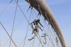 Hanging iron  figures balancing on ropes on footbridge Bernatka,Krakow, Poland Royalty Free Stock Photography