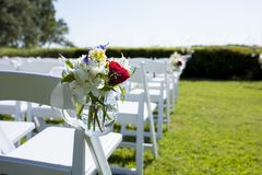 Hanging jar of flowers on chair for wedding. royalty free stock images
