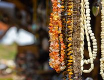 Hanging jewellery necklaces with coloured semi-precious stones, coloured stones and small white ivory pieces and amber stock photo