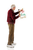 Hanging Joy. A senior man hanging a red, green and gold Joy to the World decoration for Christmas. On a white background stock photos