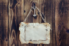Hanging key and scorched paper on a wooden background. Key hanging on a nail and scorched paper hanging on a rope on a wooden brown background Royalty Free Stock Photo
