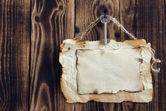 Hanging key and scorched paper on a wooden background. Key hanging on a nail and scorched paper hanging on a rope on a wooden brown background Royalty Free Stock Images