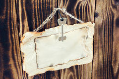 Hanging key and scorched paper on a wooden background. Key hanging on a nail and scorched paper hanging on a rope on a wooden brown background Stock Images