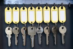 Hanging keys in metal cabinet for safety office or household keys management and keeping. keys with blank name tags, space for. Text stock image