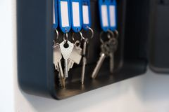Hanging keys in metal cabinet for safety office or household keys management and keeping. keys with blank name tags, space for. Text royalty free stock photo