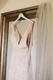 Hanging Lace Wedding Dress. Closeup of a champagne pink satin lace wedding dress hanging on a large mirror beside a veil in a bridal suite Royalty Free Stock Photos