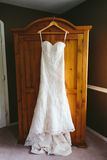 Hanging Lace Wedding Dress. A lace strapless wedding dress with a sweetheart neckline hanging on a wooden wardrobe Stock Images