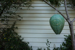 Hanging Lantern. A hanging lantern up against a house Royalty Free Stock Photo