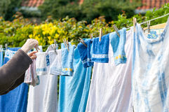 Hanging laundry outdoor. Old woman hanging laundry outdoor Stock Image