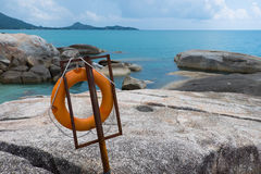 Hanging life buoy near the sea. Hanging orange life buoy near the sea Royalty Free Stock Photos