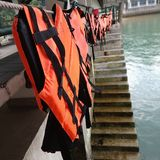 Hanging life jacket on the rope. At the pier at seaside royalty free stock photography