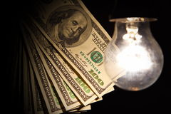 Hanging light bulb illuminating bank notes. Hanging light bulb dangle on a wire illuminating bank notes Stock Photography
