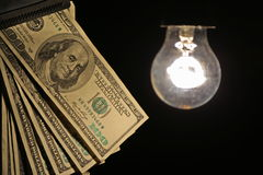 Hanging light bulb illuminating bank notes. Hanging light bulb dangle on a wire illuminating bank notes Royalty Free Stock Photo