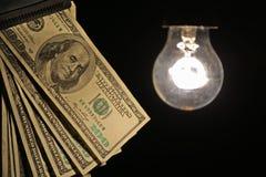 Hanging light bulb illuminating bank notes Royalty Free Stock Photo