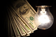 Hanging light bulb illuminating bank notes. Hanging light bulb dangle on a wire illuminating bank notes Stock Image