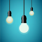 Hanging light bulbs glowing on blue background. Vector illustration. Royalty Free Stock Photos