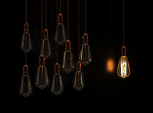 Hanging light bulbs with glowing one Royalty Free Stock Photography
