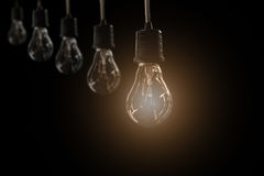 Hanging light bulbs with glowing one on dark background. Royalty Free Stock Photography