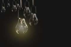 Hanging light bulbs with glowing one on dark background. Stock Images