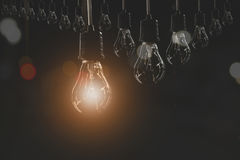 Hanging light bulbs with glowing one on dark background. Royalty Free Stock Photo