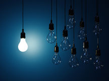 Hanging light bulbs with glowing one  on dark blue backg Stock Photos