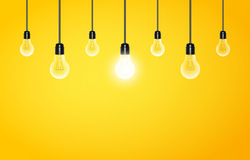 Hanging light bulbs with glowing one on a yellow background, copy space. Vector illustration for your design. Stock Photo