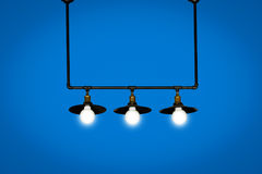 Hanging light bulbs isolated on blue background. royalty free stock photos