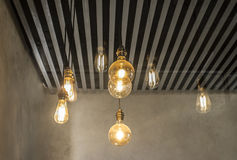 Hanging light bulbs over grey dark strip ceiling Royalty Free Stock Photo