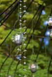 Hanging lights and crystals. Strings of twinkle lights and candles hanging from an iron gazebo. Greenery in the background, unfocused. Feeling of fairytale and royalty free stock photography