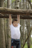 Hanging on a log. Boy in white shirt hanging on a log Royalty Free Stock Photo