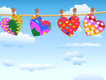 Hanging loving hearts in blue sky Stock Images