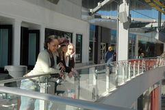 Hanging at the Mall. A trio of city women hanging at the mall looking at people walking below. Friends hanging on the rail at the mall having fun Royalty Free Stock Photo